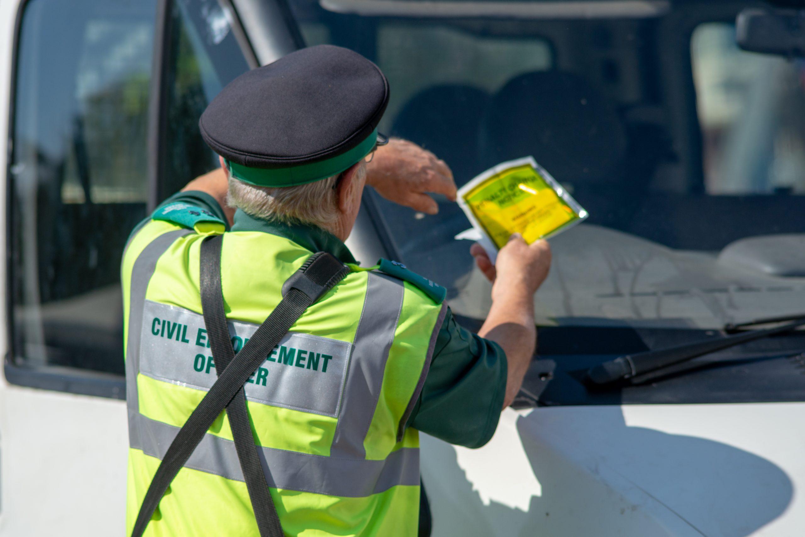 Warden gives parking fine to van
